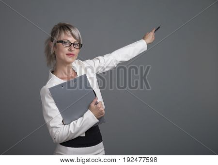 Portrait of beautiful young woman with phone and blank signboard, dressed in pin-up style. Caucasian blond model posing in retro fashion and vintage concept studio shoot, on grey background