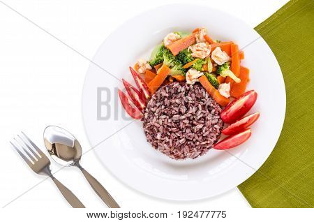 Healthy homemade dish with brown & red rice stir-fried shrimp carrot broccoli & fresh sliced tomato on white plate over cotton place mat with silver fork and spoon on white background for good health
