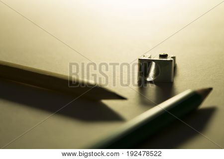 Two pencils and a pencil sharpener on the paper backlight