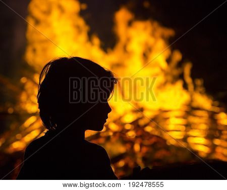 Silhouette of child in front of a fire.