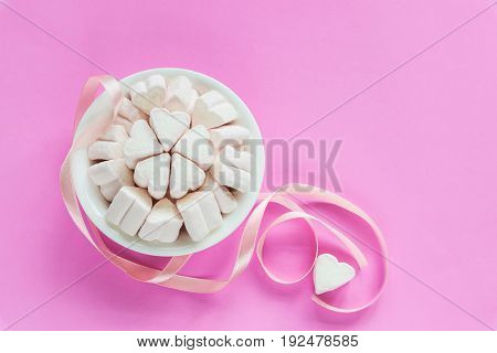 Marshmallows in heart shapes for Valentines day in white ceramic bowl over pink paper background with cute ribbon to show sweet love candy for couples on special time in holiday season