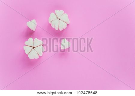 Marshmallows in heart shapes for Valentines day over pink paper background grouped like sakura flower to celebrate sweet love candy for couples