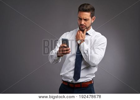 A handsome young man feeling upset while holding and looking at his smartphone