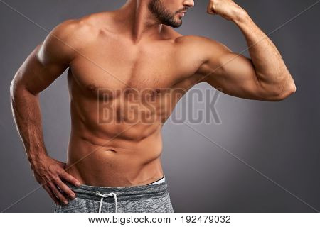 Closeup look from a young sportsman upper body while he is showing his biceps