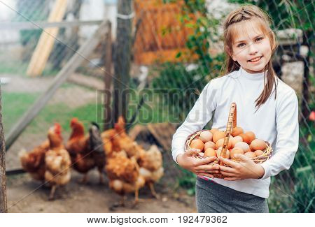 little cute girl holding in hands a basket full of fresh eggs.