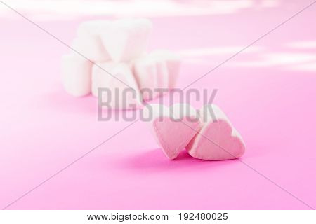 Marshmallows in heart shapes for Valentines day over pink paper background with soft sunlight at the back to celebrate sweet love candy for couples selective focus