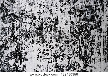 Abstract textured background in black and white, the base of the concrete electric pole whitewashed with lime