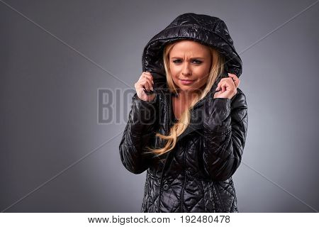 A beautiful young woman standing in a winter jacket and feeling sad