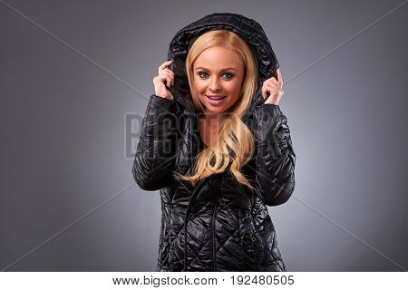 A beautiful young woman standing in a winter jacket and holding the hood of it