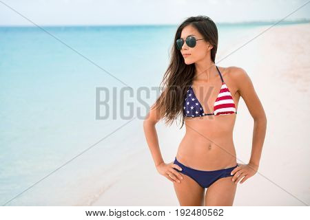American USA flag bikini girl beach party vacation on summer holidays. Sexy Asian woman with slim body wearing fashion swimsuit for 4th of July independence day celebration.