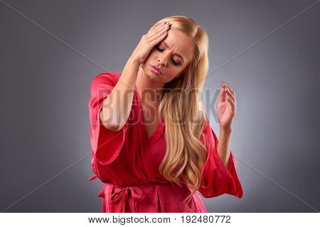 A beautiful young woman having a headache and grabbing her head in a pink robe
