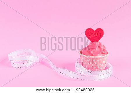 Sweet homemade cupcake with red heart shaped fondant over pink background with white ribbon and copy space for text decoration