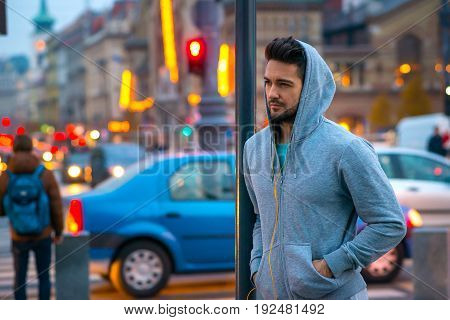 A handsome young sportsman leaning to a pillar on the street with the car lights behind him