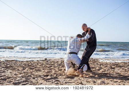 two young fit mans training karate on the morning summer beach