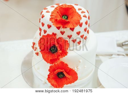 beautiful wedding cake with red poppies and hearts