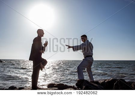 two male karate fighters in black and white clothes posing during sunrise