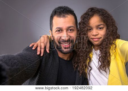 Camera view of a black father and his young daughter smiling and taking selfie