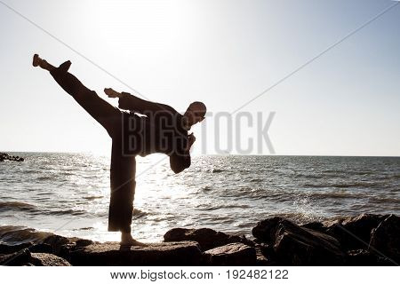 male practicing karate on the beach on a sunny day