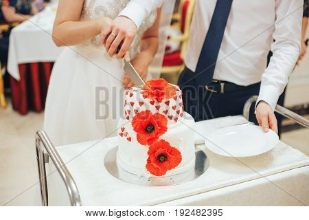 the hands of the newlyweds holding a knife that cut a beautiful wedding cake decorated with red poppies and hearts