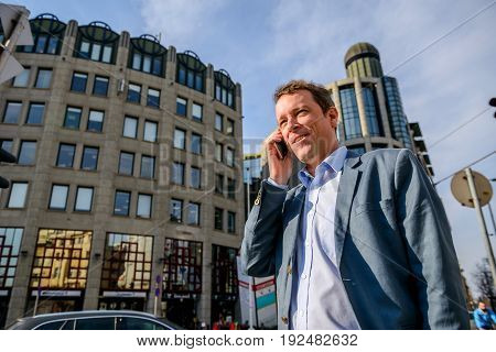 Close up look of a middle age businessman standing in front of the office building while talking on his phone