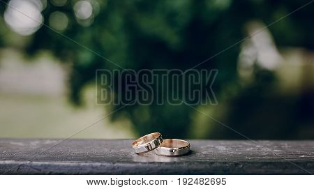 wedding rings lie on a wooden surface