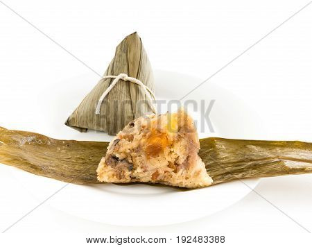 Chinese rice dumpling (Zongzi) stuffed with peanuts mushroom sweet mashed taro marinated steamed pork Ginkgo Biloba and salted egg yolk over bamboo leaf and white plate on white background