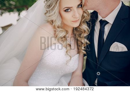 Bridal veil wedding couple hugs kisses outdoors
