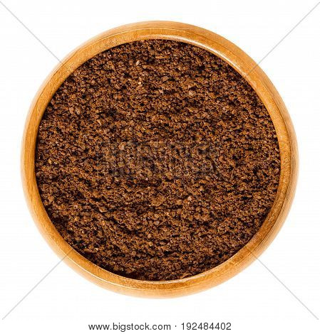 Fresh coffee powder in wooden bowl. Ground Arabica coffee beans. Roasted brown pits of coffee cherries. Caffeine. Isolated macro food photo close up from above on white background.