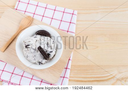 Cookies and cream ice cream on wooden table and white and red stripe napkin with spoon top view and copy space of wood background