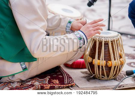 man plays on classical drums of Tajikistan