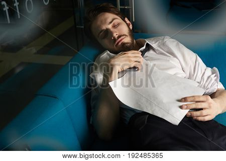 Overworked banker with smartphone and paper asleep on sofa in his office
