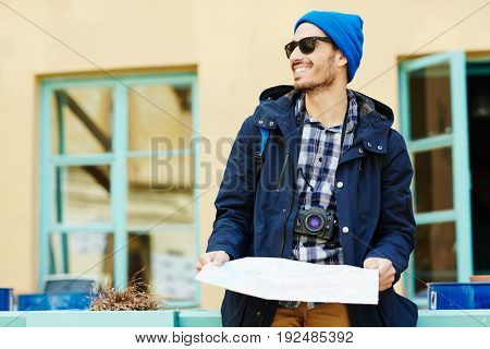 Backpacker with map and photocamera enjoying trip