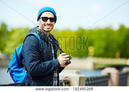 Young backpacker with rucksack and photocamera