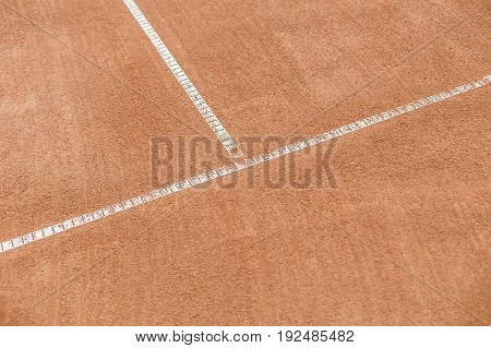 Orange tennis court. White lines on a brown field for a game.