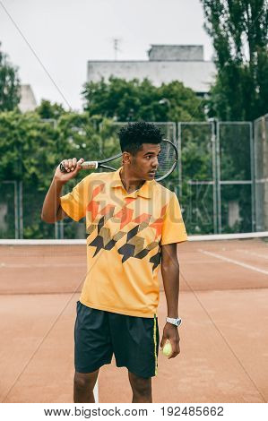 Young black man is holding a tennis racket on his shoulder. Portrait of a pensive man in sports wear and tennis racket looking away.