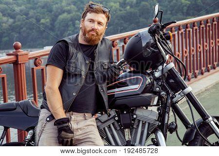 Redhead biker with beard in leather jacket near his bike.