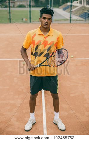 Full leg portrait of tennis player man. Front view african man looking at camera on the court.