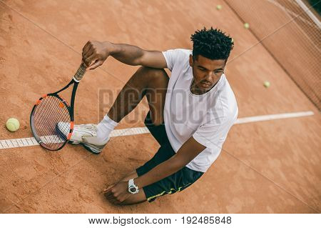 Exhausted male tennis player sitting on ground after tennis game. African man resting and chilling on the break time.