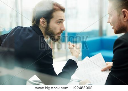 Two young traders discussing business papers