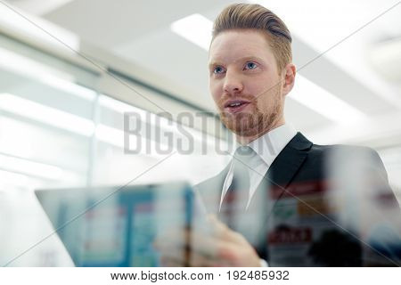 Confident trader with touchpad talking to someone