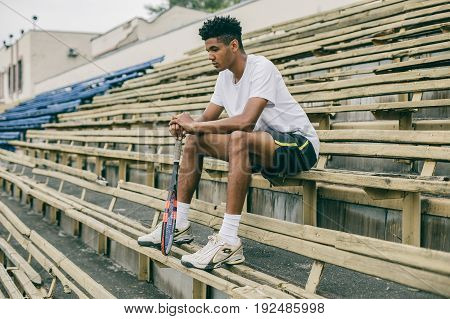 Picture of handsome young man on a bench. Man relaxing after tennis play. Man sitting on bench.