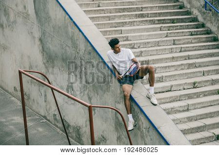 An athlete with a tennis racket sits on a concrete railing of steps. A young black guy rests after a professional competition.