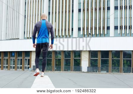 Back view of active man moving in urban environment