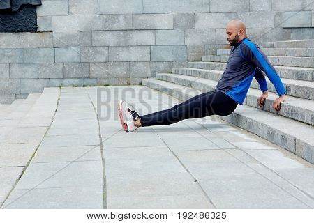 Active man doing physical exercise on staircase in urban environment