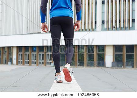 Rear view of sportsman walking towards urban edifice