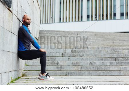 Sporty guy in headphones leaning against wall while exercising outdoors