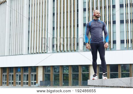 Sportsman with headphones on background of modern architecture