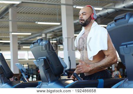 Sporty man jogging on treadmill in gym