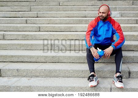 Restful sportsman with headphones and bottle of water sitting on stairs outdoors