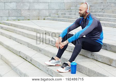 Young man in activewear sitting on stairs and listening to music in headphones